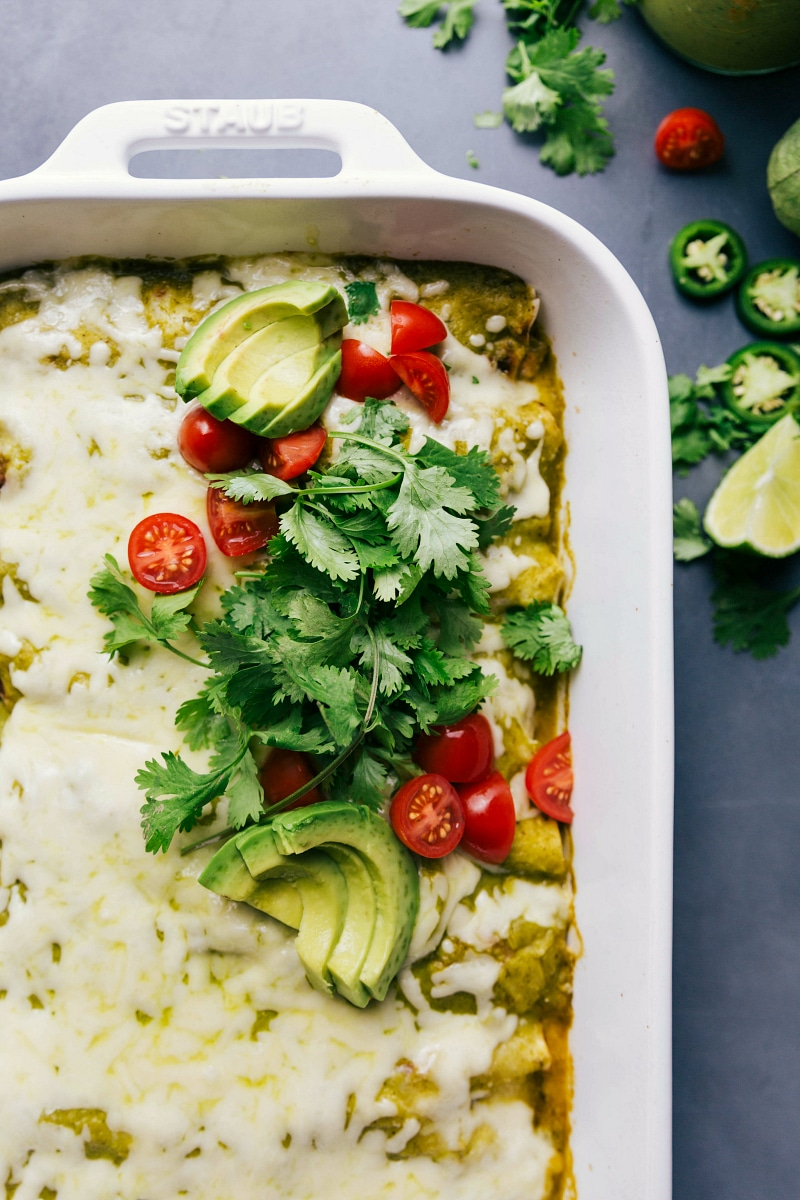 View of the toppings for Green Chile Chicken Enchiladas: cilantro, tomatoes and avocado.