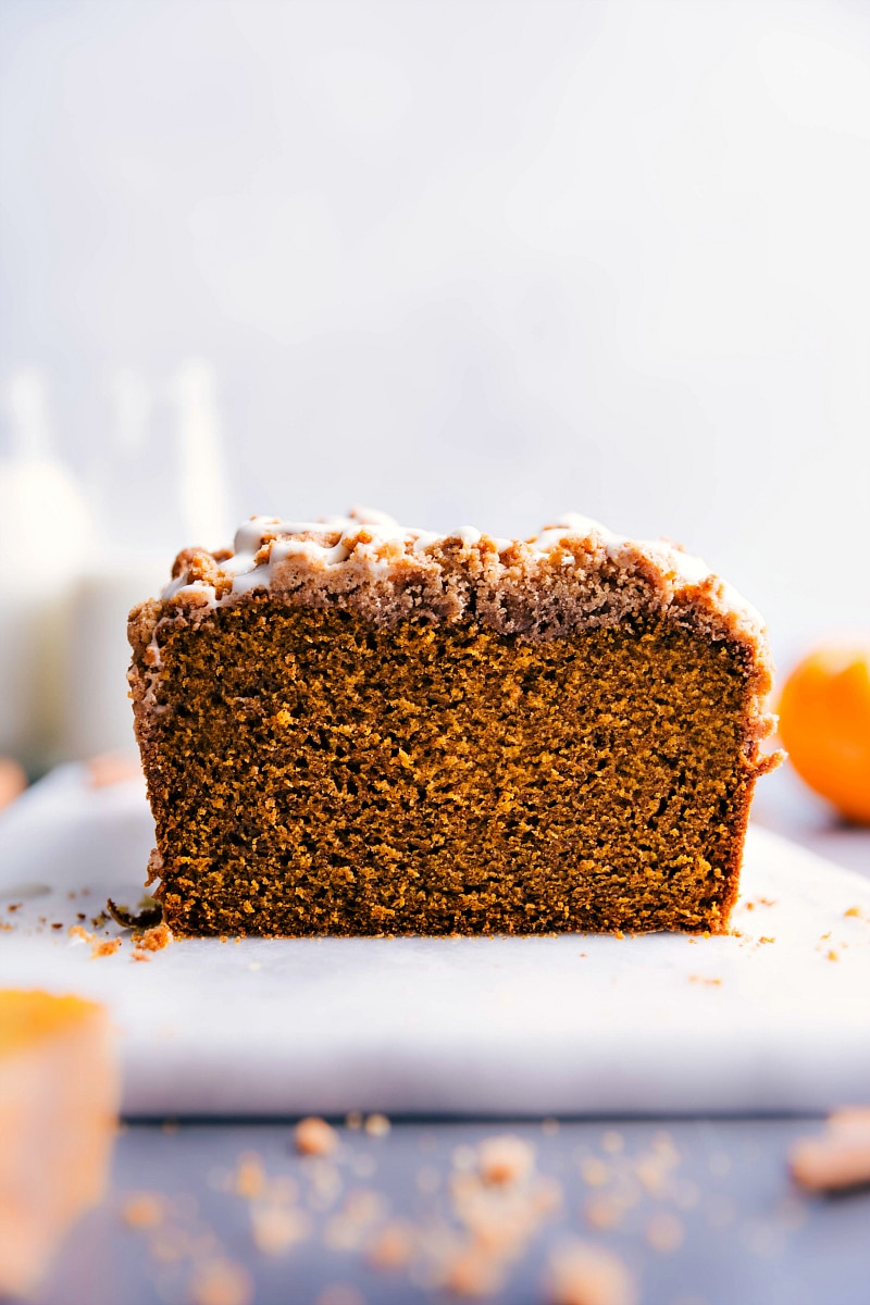 Image of a loaf of Pumpkin Bread With Streusel Topping with a slice out of it.