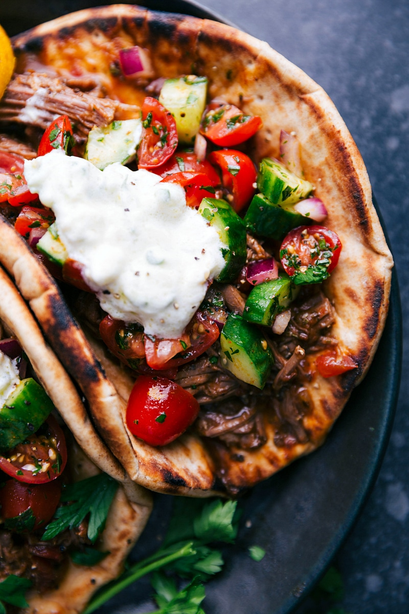 View of the folded Beef Gyro, showing the tzatziki sauce, salad and meat.