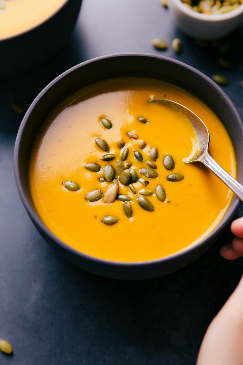 Up-close overhead image of Carrot Soup in a bowl with someone taking a spoonful out of it.