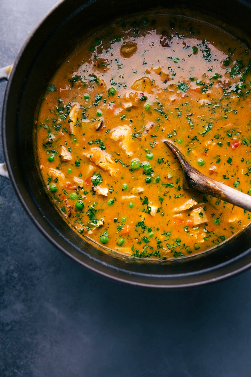Overhead view of a pot of Chicken Curry Soup being stirred with a wooden spoon.