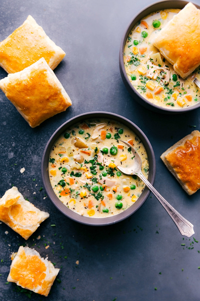 Overhead image of two bowls of Chicken Pot Pie Soup with the fresh puff pastry scattered around the bowl.