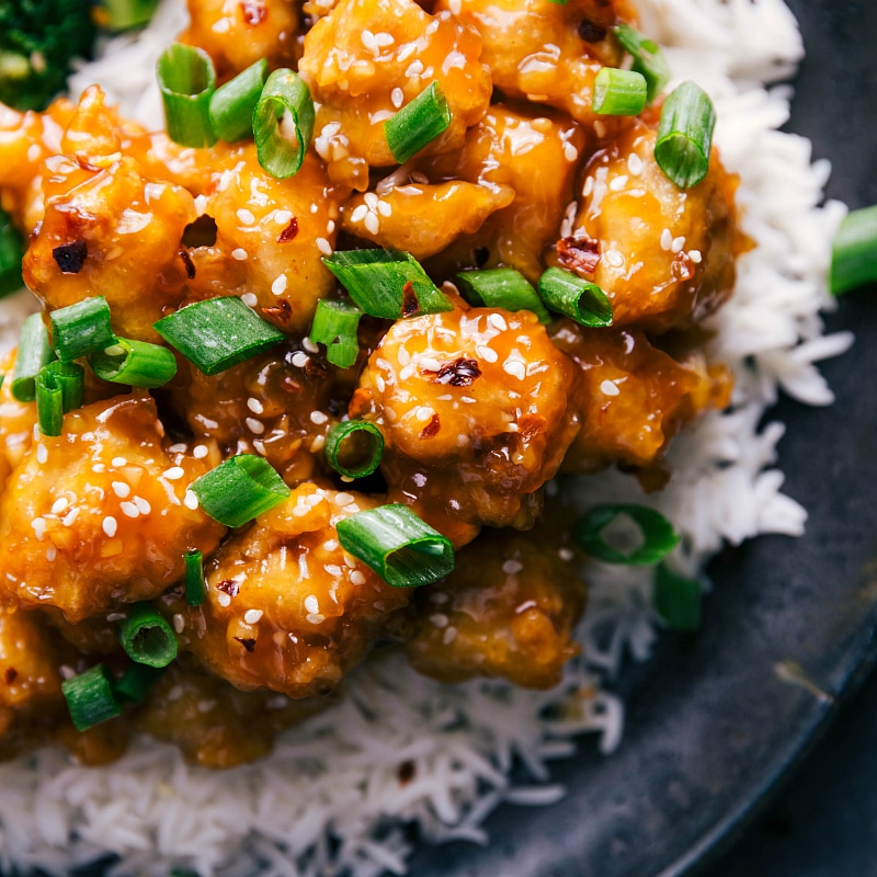 Orange Chicken, served with rice and garnished with sesame seeds and green onions