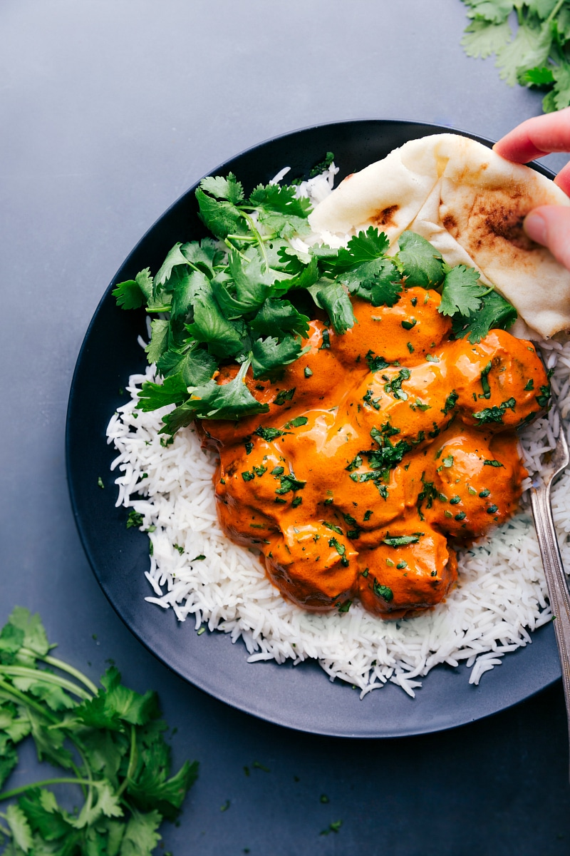 View of a plate with Butter Chicken Meatballs on a bed of rice, garnished with cilantro and naan bread on the side.