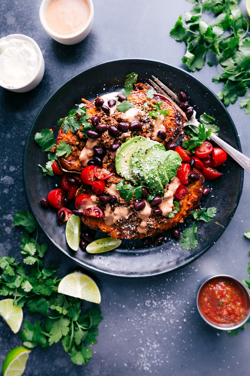 Overhead view of Taco-Stuffed Sweet Potatoes on a plate, with salsa on the side.