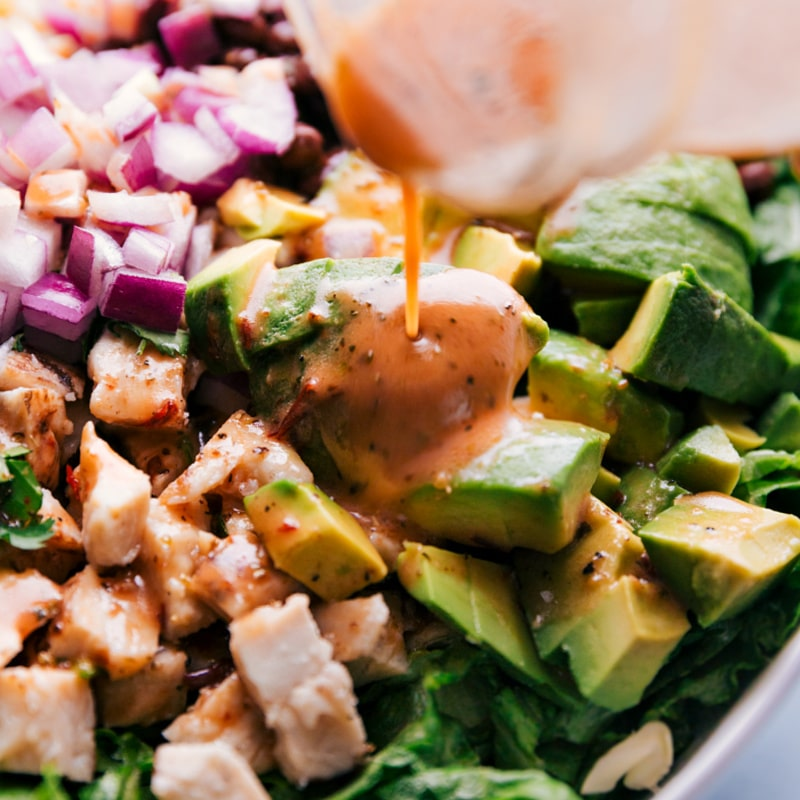 Close-up view of the chipotle-lime vinaigrette being poured over the salad.
