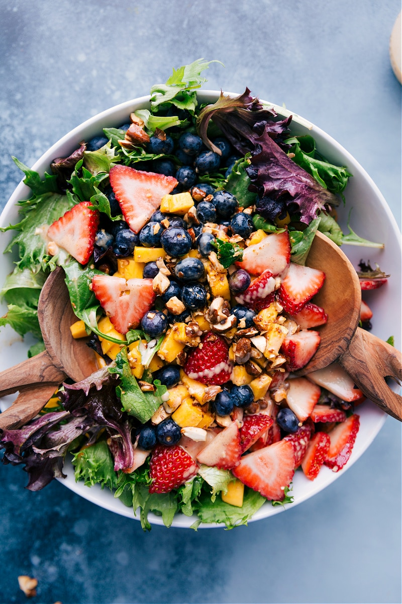 Overhead view of Mango salad with blueberries and strawberries.