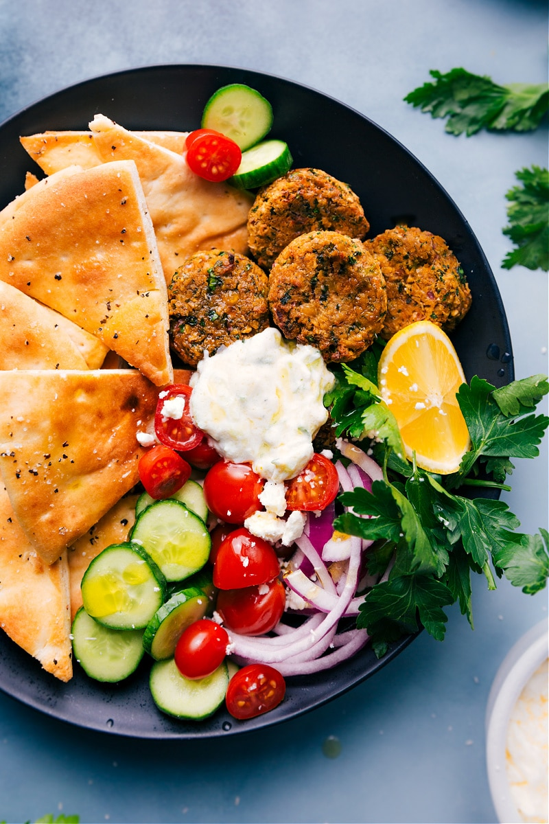 Overhead image of the Air Fryer Falafel, pita triangles, tzatzki, and raw veggies on a plate