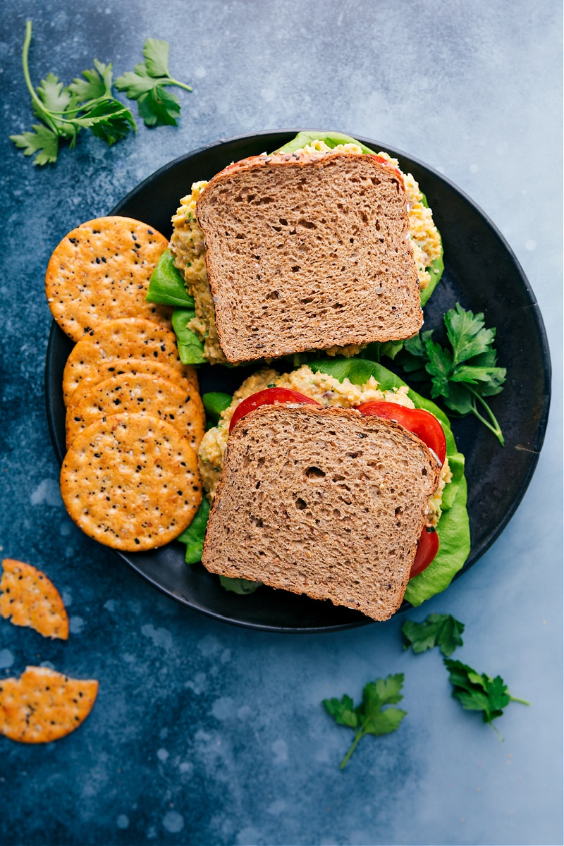 Overhead image of two of the vegetarian tuna sandwiches on a plate with crackers on the side
